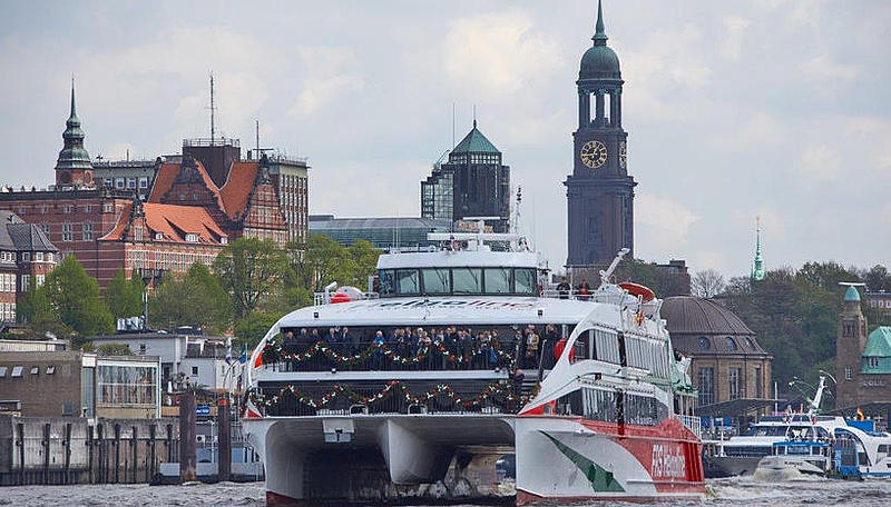 The Halunder Jet decorated for its launching ceremony with the skyline of Hamburg in the background